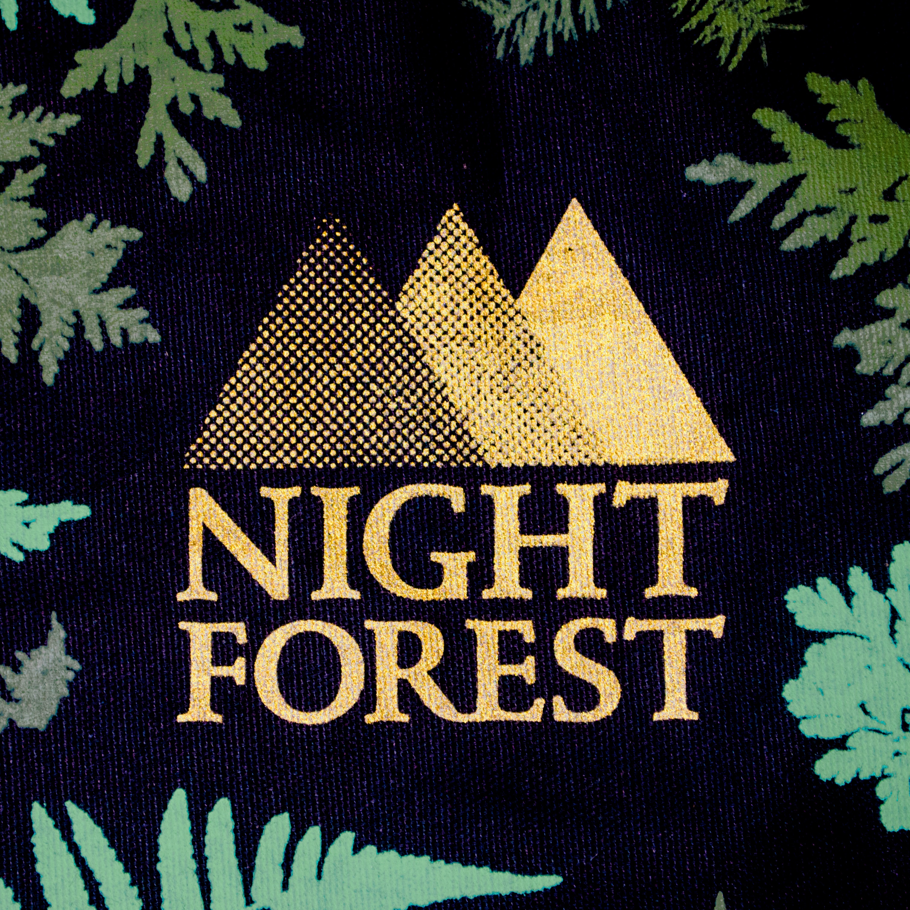 Night Forest logo, screenprinted in gold on a black fabric with dark teal branches around